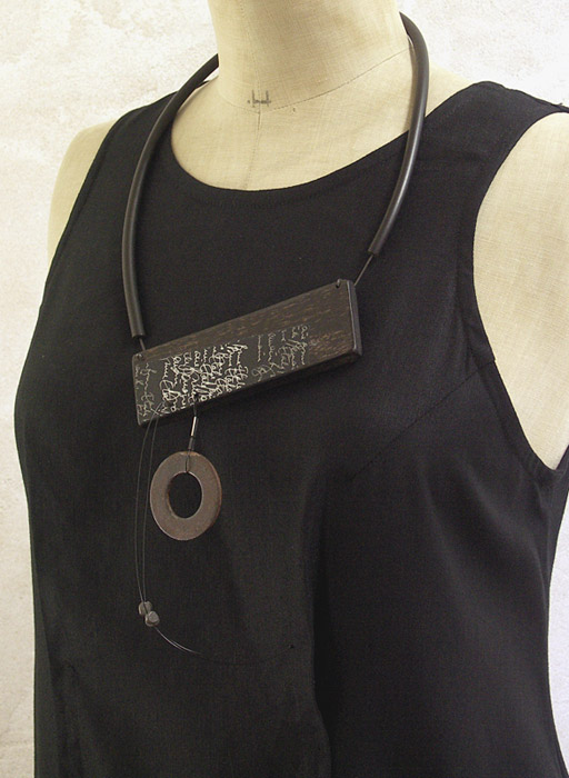 Necklace made of ebony, hand written paper, oxidized iron, rubber [category]